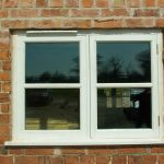 cottage style window with white wood trims red bricks wall system