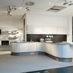 curved kitchen island with stunning chairs and steel countertop plus glass and sink and art display combined with cool lighting