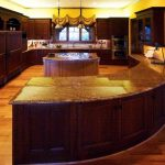 curved kitchen island with wooden cabinets with granite countertop plus and wooden laminating floor and kitchen appliances