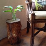 darker staining tree stump table with small glass with green plants a craftman wood chair with mattress seating and pillow wood planks floor system
