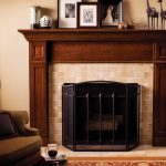 Darker Staining Wood Fireplace Mantel  For Wood Burning Fireplace With Metal Door A Luxurious Corner Chair With Dark Brown Pillow Some Pictures Frames On Top Of Mantel