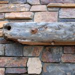 driftwood mantle installation for outdoor fireplace