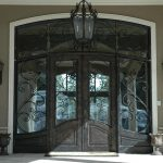 Elegant Black Front Door Design With Double Wood And Glass Panels And Windows On Top And Sides Combined With Gray Wall And Wall Scones Plus Chandeliers