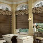 elegant brown rolled window blind design with floral pattern top design on arch window in bathroom with white bathtub and wooden bench and white storage
