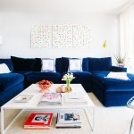 elegant dark blue L shape sofa which is cat's claws resistant several white decorative pillows a white table for living room with a lot of books collections  pure white carpet white-cap standing lamp