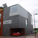 facade black and white brick wall with large glass windows plus car garage and red brick wall