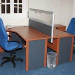 face to face L shape tablestation for two persons with divider blue office chairs with wheels a basket for garbage