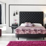 floral patterned bedding idea beneath tall decorative black tufted headboars above white pillows between black nighstand beneath table lamps with purple area rug