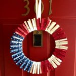 fourth of july wreath design made of clothes pin in round modern with red white and stars patterned blue with white ribbon hanging on red door of 301