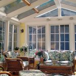 fresh large sunroom design with glass ceiling and white framed glass window and door upon patterned chairs design with wooden frame with greenery