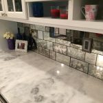 glass tiles backsplash in different size  white granite countertop a small capture frame in white a small decorative pot with beautiful flowers open shelving unit a glass door top storage with handle