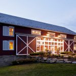 gorgeous pole barn house design with reddish wall idea with flashing white accent for windows and doors with brick and natural stone foundation and garden with grassy meadow