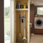 gorgeous white broom closet design with yellow inner and broom hooks and rack for cleanser solution
