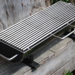home hibachi grill with firm stainless steel stick and triple handles on right left and front side with black frame upon rustic log in outdoor space