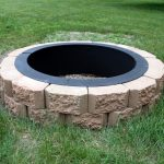 in-ground fire pit in round shape with permanent brick frame built