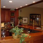indoor porch with furnished cabinetry with greenery and glass wine and reccessed lamps on white ceiling above wine racks aside the upper cabinet