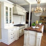 inexpensive walnut wood kitchen island countertop with white storage beneath luxurious golden chandelier aside white cabinetry upon beige bamboo flooring design