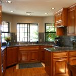 kitchen remodeling with brown modern wood cabinets plus marble countertops and backsplashes and sink combined with wood floor