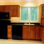 kitchen remodelling contractors for small kitchen with wooden cabinets and tile floor and sink plus black countertop and glass windows