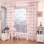 korean patterned pink curtain design with shade and pink metal rod above small storage with small table and chair upon wooden floor