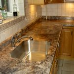 laminate kitchen counter that mimics marble finishings a deep stainless steel sink and faucet white ceramic backsplash