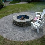 large landscape design with grassy meadow and center in ground fire pit design made of stone with white wooden lawn chairs and wooden table