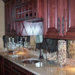 large size diagonal mirror tiles backsplash small round sink and dark bronze faucet  two snack containers luxurious and expensive marble countertop dark stained wood top cabinets