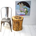 large tree stump side table a plastic chair in grey color a cute rabbit painting