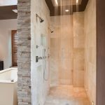 large walk in shower no door with high and large ceiling shower head warm and light cream natural stone tiles for floors and wall system  a pair of wall mounted shower heads a bathtub