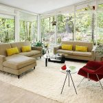 light brown sofas with yellow pillows a glass top table white fury carpet a red chair with tiny metal legs a round glass surface side table with metal legs