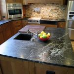 luxurious and expensive black soapstone kitchen island with square sink and faucet  and also a cut board