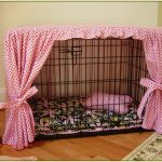 luxurious dog crate with pink curtains and pink pillow plus dark bedding