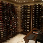 luxurious wine cellar desuign with plenty of wine bottles stacked on wooden racks before wooden table with black bench beneath small recessed ceiling lamps