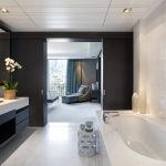 luxury architecture interior design for bathroom with modern bathtub and vanity units with sink and mirror plus exclusive marble wall and floor