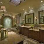 luxury master bath remodel with classic vanity units and mirror plus sinks and glamour wall scones and bathtub