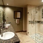 master bath remodel with glass walk in shower plus vanity units with granite countertop and mirror plus pretty green vase and mirror plus sinks
