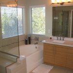 master bathroom remodel with bathtub and walk in shower with glass and wooden vanity unist plus mirror and sink and decorative displays plus windows with blinds