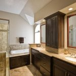 master bathroom remodel with large vanity units plus double sinks and bathtub and walk in shower with glass and natural tile flooring plus ceiling lamp