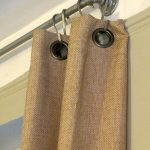 metal half curtain rod with hooks and brown curtain
