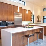 mid century kitchen remodel with wood kitchen cabinet system a white-top kitchen island with chairs and sink  plus faucet artistic pendant lamp sets