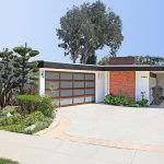 mid century modern garage doors with glass and wood material for two cars combined with brick wall and small garden