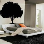 minimalist bedroom design with grey bedding set upon black furry area rug and flashing orange pillow beneath unique tree hedboard decoration idea
