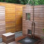 minimalist outdoor shower space with horizontal wood planks wall system stainless steel free standing shower head a wood shower bench a small wet area