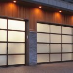 moden two car garage door with aluminum and glass door material plus lighting and wood wall