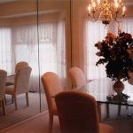 Modern And Exclusive Dinig Room With Luxurious Cream Seating And Rectangle Glass Table With A Vas Of Flower Beneath Chandelier With Floor To Ceiling Mirror