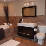 modern bathrooms remodeling with bath tub plus bathroom vanity units with sink and mirror plus toilet and wall scones and shower room with glass wall
