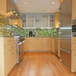 modern galley kitchen remodel with beige tone and flashing green tile backsplash and sunflower with wooden flooring idea and modern lighting