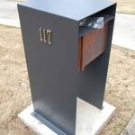 Modern Mail Box Design Made Of Metal In Grey Tone With Wooden Box Inserted With 117 Code Number Above White Concrete Base Upon Ground