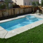 modern rectangle pool designs with cool natural stones edges and outdoor chair together with umbrella at green garden