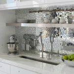 mosaic tiles mirror kitchen backsplash white porcelain kitchen countertop pure white bottom kitchen cabinets glas door top kitchen cabinets  a floating single shelf square metal sink and faucet